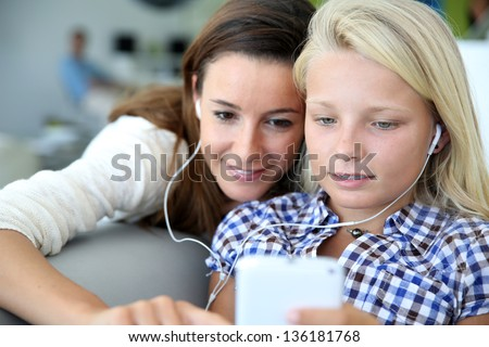 Teenager and woman listening to music with smartphone - stock photo
