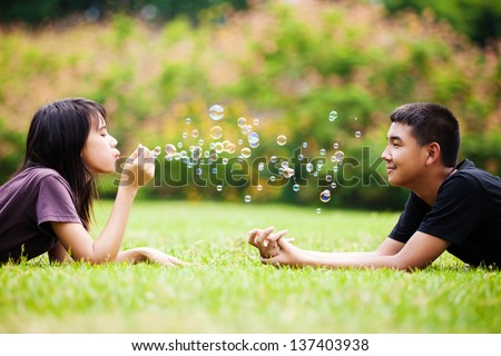 Teenager asian girl blowing soap bubbles for brother - stock photo