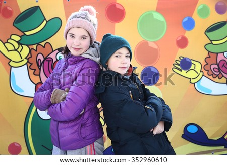 teenager boy and girl in winter jackets and knitted woolen hat on th circus wall background with clowns balloons drawing happy smiling close up portrait together - stock photo