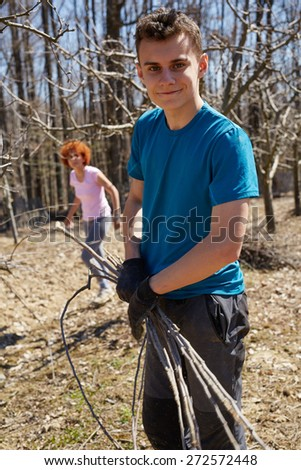 Teenager boy and his mother spring cleaning the orchard, gathering cut branches to throw them away - stock photo