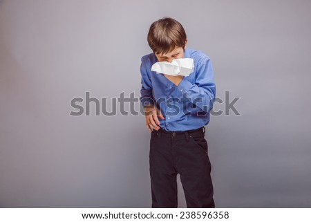 teenager boy blowing his nose brown hair of European appearance in a handkerchief experiencing discomfort on a gray background - stock photo