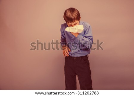 teenager boy blowing his nose brown hair of European appearance in a handkerchief experiencing discomfort on a gray background retro - stock photo