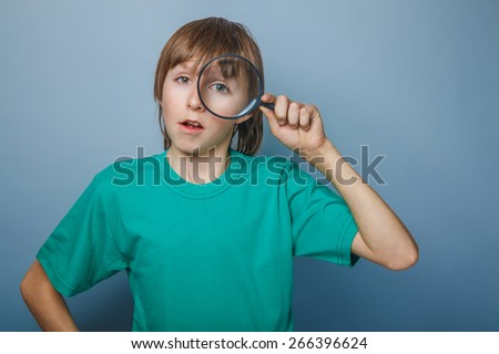 teenager boy brown European appearance in a green shirt looking through a magnifying glass eye opened his mouth on a gray background, knowledge, curiosity