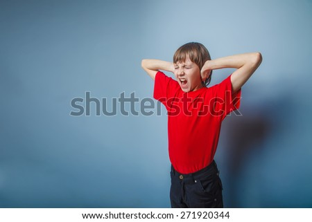 teenager boy brown European appearance in a red shirt hands covering his ears shouting on gray background, fear, scream - stock photo