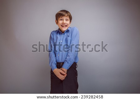 teenager boy brown hair European appearance laughing and looking away with hands clasped, joy