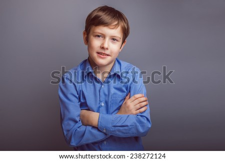 teenager boy brown hair European appearance smiles experiencing joy on a gray background