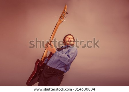 teenager boy brown hair of European appearance playing guitar feels joy on a gray background retro - stock photo