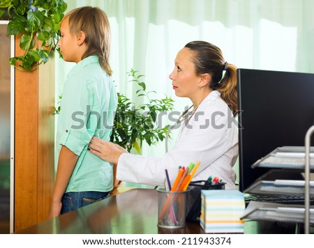 Teenager boy complaining of pain in behind to female doctor - stock photo