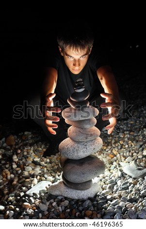 teenager boy conjuring near pyramid from pebble on stony seacoast at night - stock photo