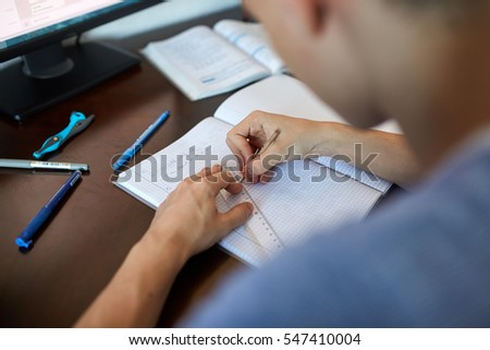 Teenager boy doing homework on his desk at home