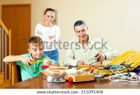 Teenager boy doing something with working tools, parents are watching at home - stock photo