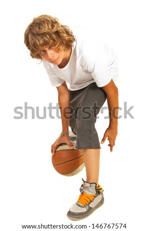 Teenager boy dribbling basketball isolated on white background - stock photo