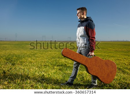 Teenager boy guitarist with his guitar in a hard case outdoor - stock photo