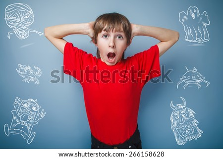 teenager boy in red T-shirt European appearance brown hair opened his mouth keeps his hands at his face on a gray backgroundunexpectedness, surprise