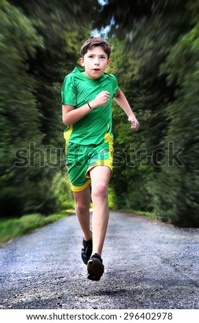 teenager boy in sportswear run on the country road - stock photo