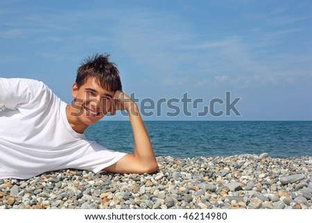 teenager boy in white T-shirt lying on stony seacoast - stock photo