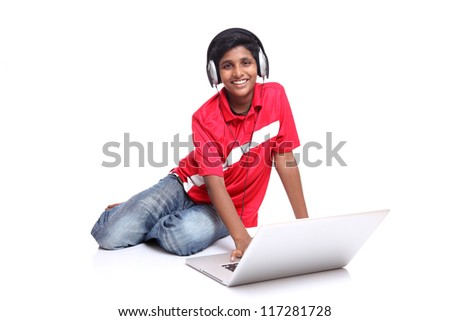 teenager boy is sitting with laptop on white background. - stock photo
