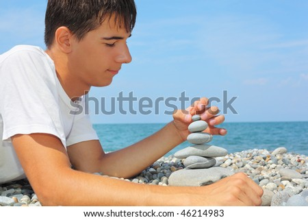 teenager boy lying on stony seacoast, creates pyramid from pebble, Looking at pyramid - stock photo