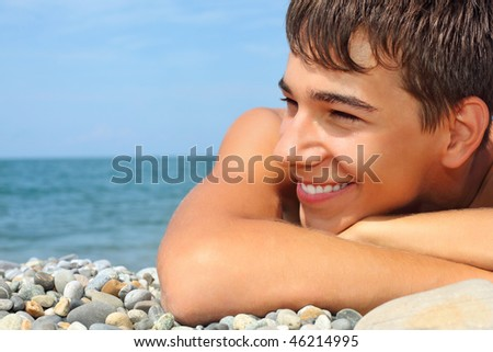 teenager boy lying on stony seacoast, looking afar - stock photo