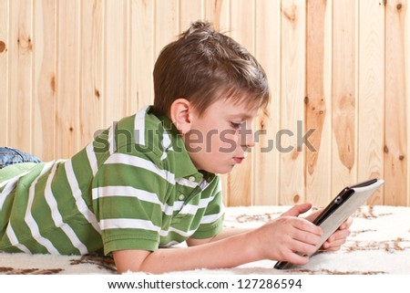 teenager boy lying on the bed with a Tablet PC - stock photo