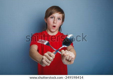 teenager boy of fourteen European appearance with a spoon fork and smiling - stock photo