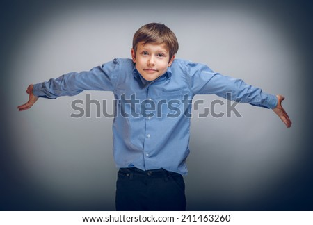 teenager boy of 10 years of European appearance spread his hands, confusion cross process - stock photo