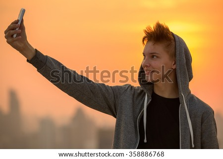 Teenager boy outdoors taking selfie with mobile phone