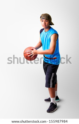 Teenager boy playing with basket ball on grey background with clipping path