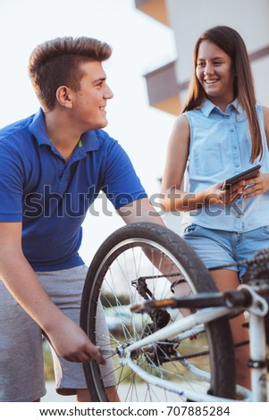 Teenager boy repair tire on bicycle , female friend standing next to him, using digital tablet for instructions, summer outdoor photo