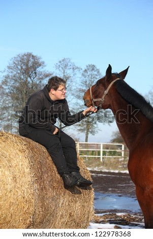Teenager boy resting on the hay bale and bay horse portrait in winter - stock photo