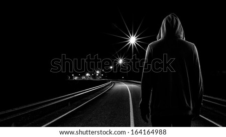 Teenager boy standing alone in the street at night, Black & White tone - stock photo
