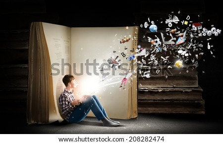 Teenager boy wearing jeans and shirt and reading book - stock photo