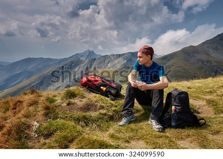 Teenager boy with backpack hiking on a mountain trail - stock photo