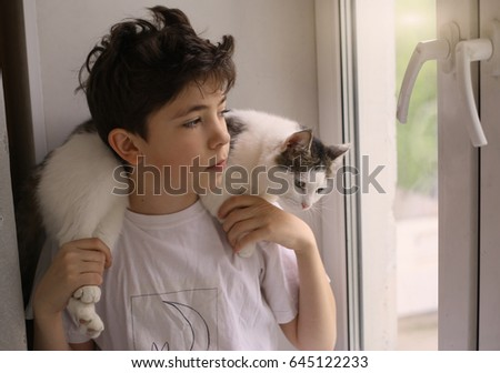 teenager boy with cat on his shoulders close up photo on window background