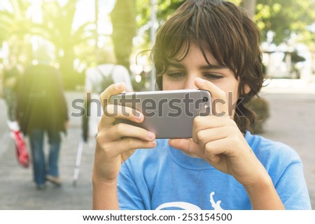 teenager boy with making photo with smartphone on street - stock photo