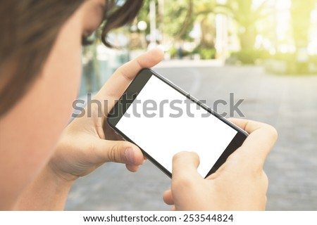 teenager boy with smartphone on street, copy space on blank screen - stock photo