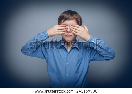 teenager boy 10 years brown hair Caucasian appearance eyes closed hands on a gray background cross process - stock photo