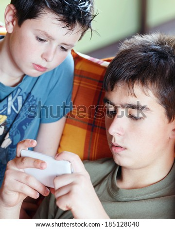 Teenager boys playing on smartphone, outdoor with shallow focus - stock photo