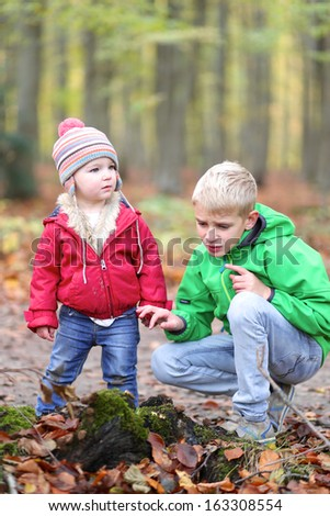 Teenager brother and toddler sister playing in the forest saving little insects - stock photo