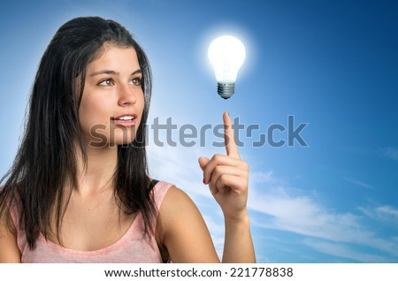Teenager brunette girl pointing her finger to a light bulb - stock photo
