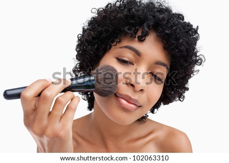 Teenager carefully applying make-up powder with her black brush - stock photo