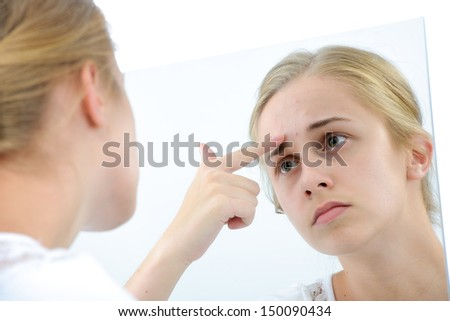 Teenager checking her face for pimple in the mirror - stock photo