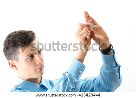 Teenager concentrated looking at a micro chip isolated on white  - stock photo