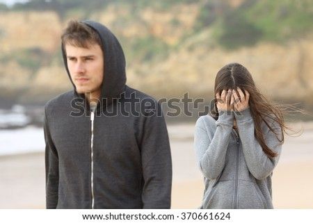 Teenager couple breaking up. The angry boyfriend leaves his sad girlfriend - stock photo