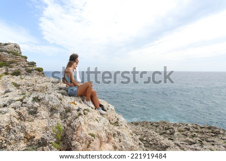 Teenager couple hugging and looking at horizon on a cliff