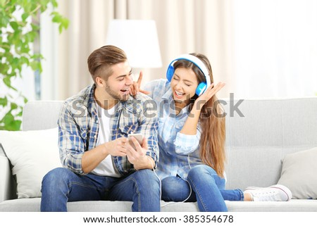 Teenager couple listening to music with mobile phone on a sofa - stock photo