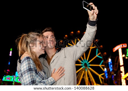 Teenager couple using a smartphone cell mobile to take a photograph while visiting an attractions park at night, with colorful lights and rides in the background. - stock photo