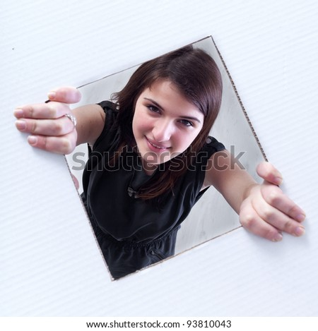 Teenager crawling and peeking out of a rectangular hole in cardboard layer - stock photo