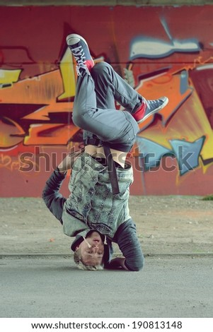 Teenager dancing break dance on the street - stock photo