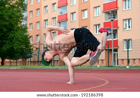 Teenager dancing breakdance in the street - stock photo